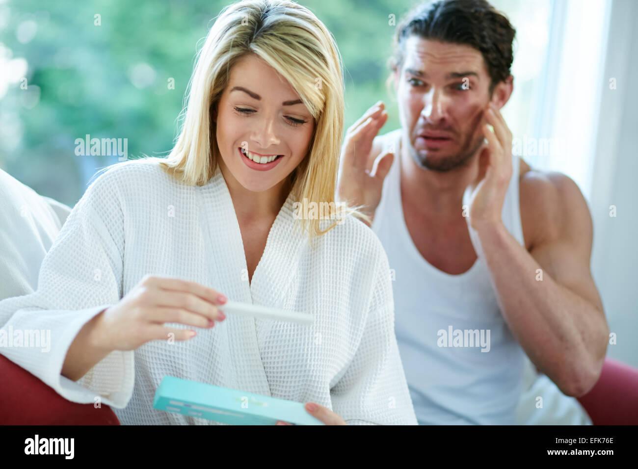 Glückliches Mädchen finden heraus, dass sie schwanger ist verärgert Mann im Hintergrund Stockbild