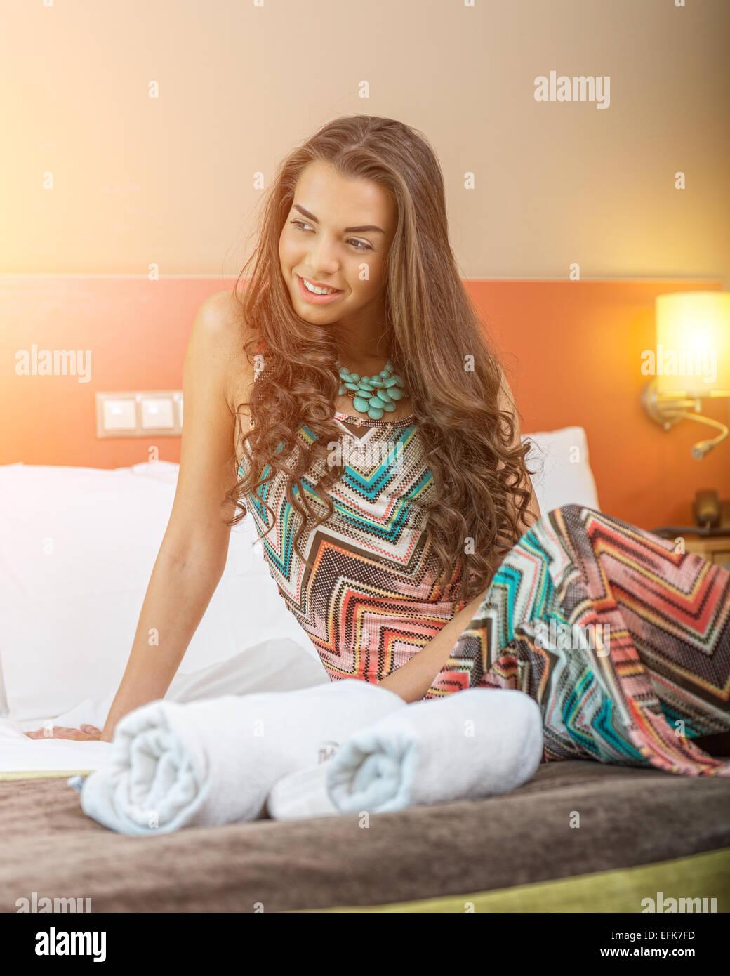 Junge Frau sitzt in dem Bett eines Hotelzimmers Stockbild