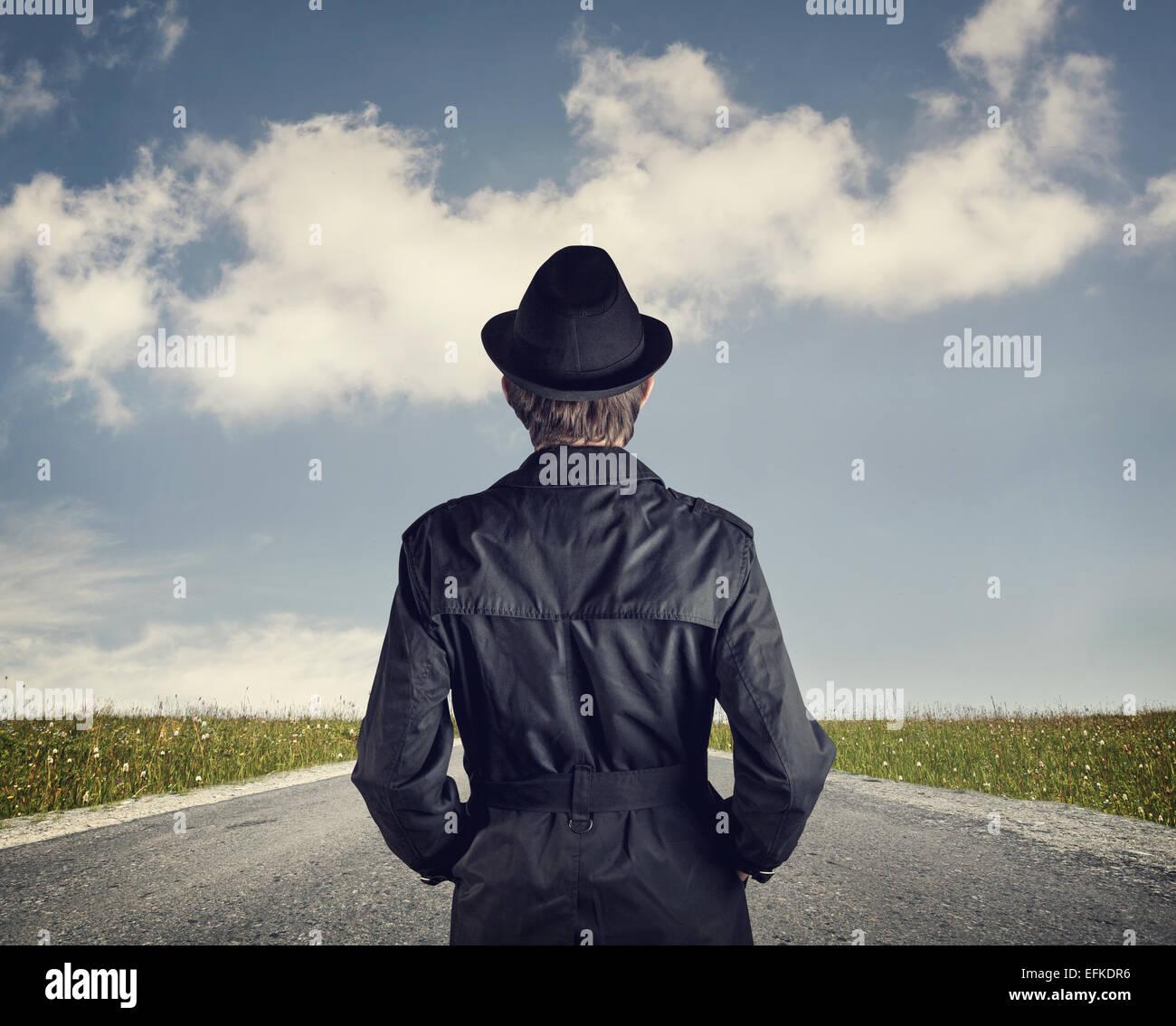 Mann im schwarzen Hut auf der Straße bei bewölktem Himmelshintergrund Stockbild