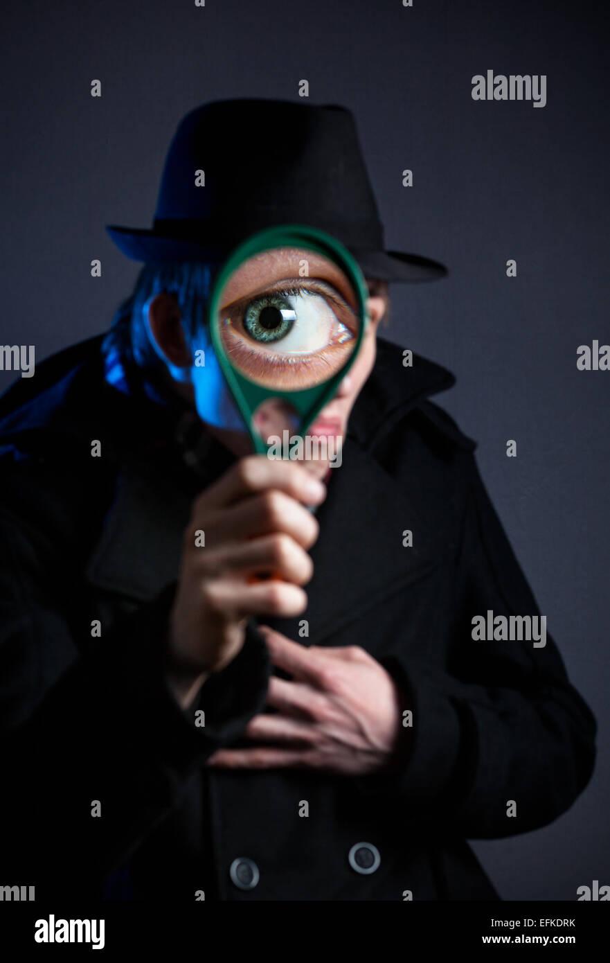 Mann im schwarzen Hut mit Lupe auf dunklem Hintergrund Stockbild