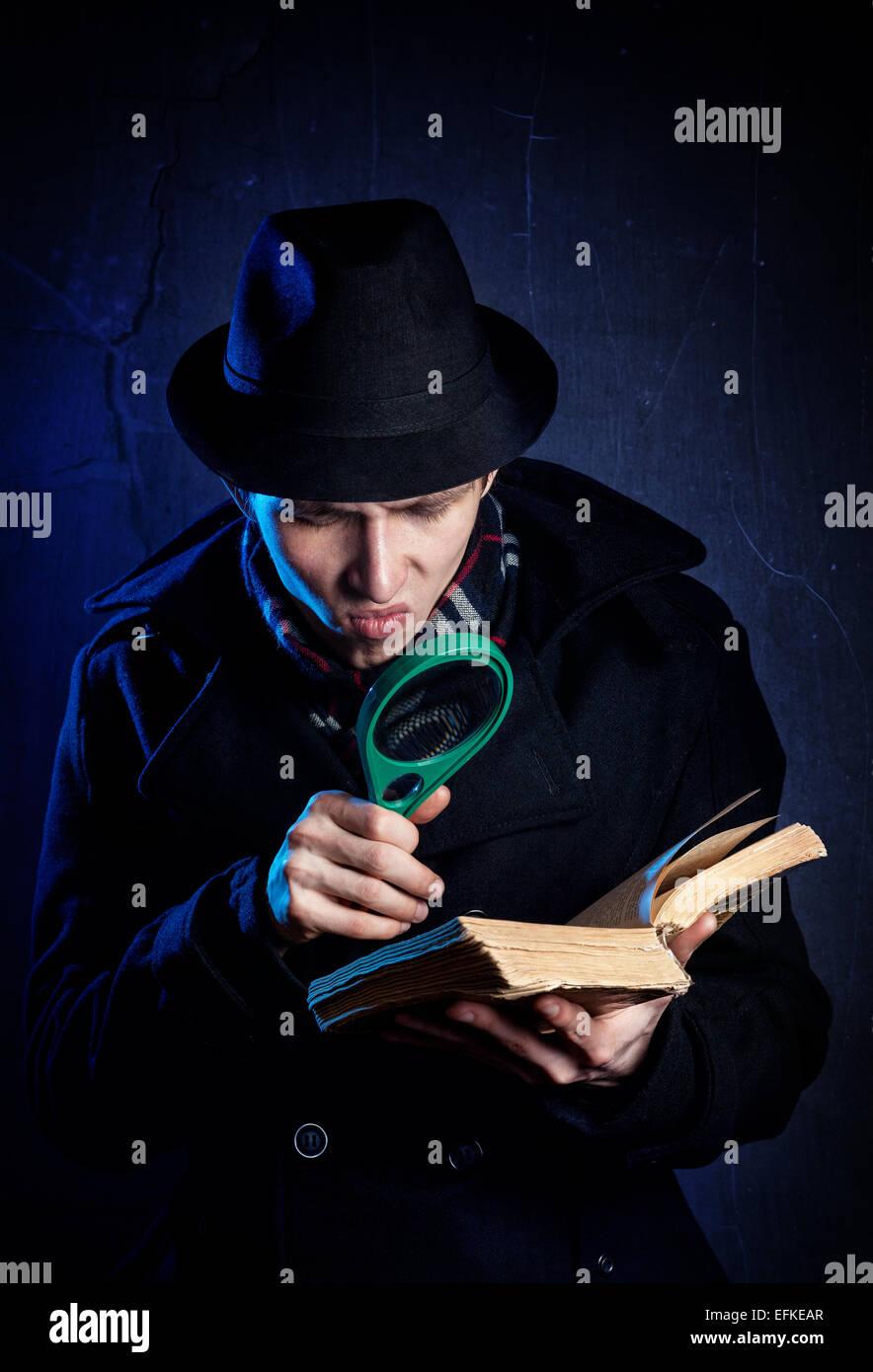 Mann mit schwarzem Hut mit Lupe, die das alte Buch bei dunklem Hintergrund Stockbild