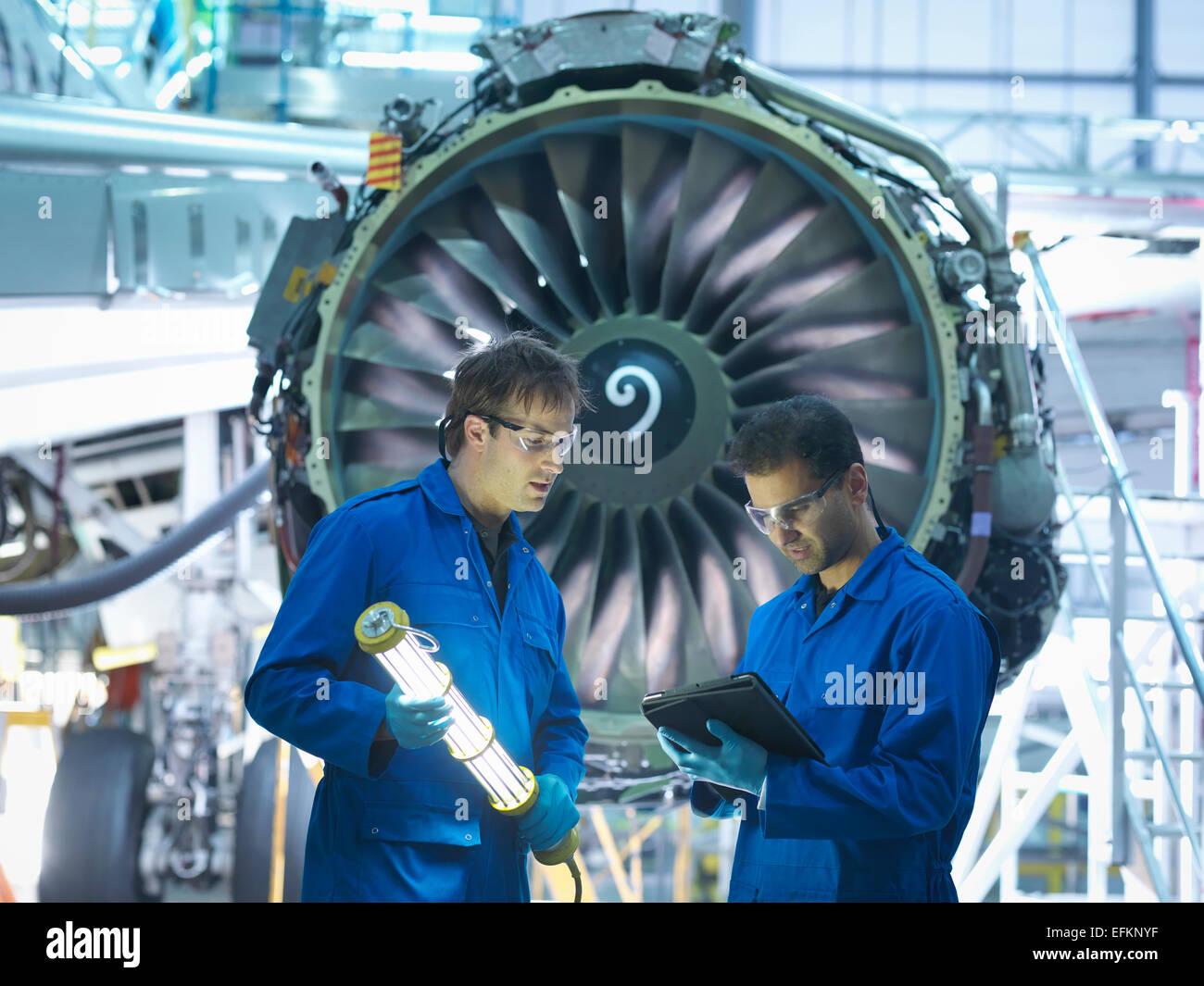 Flugzeugingenieuren Wartung Details über digital-Tablette vor der Jet-Engine in Wartung Flugzeugwerk zu diskutieren Stockbild