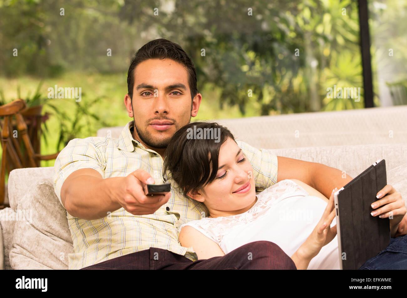 süßes Paar kuscheln auf dem Sofa beim Fernsehen und mit