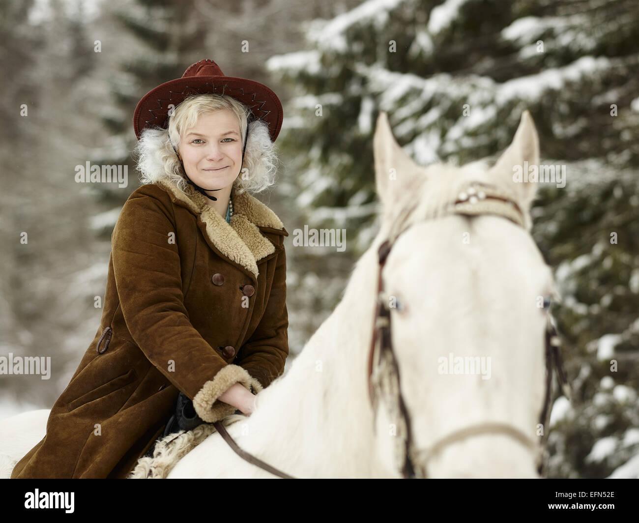 Attraktive Frau trägt einen Winterjacke und Hut, sie Reiten ein weißes Pferd und sie sieht in die Kamera Stockbild