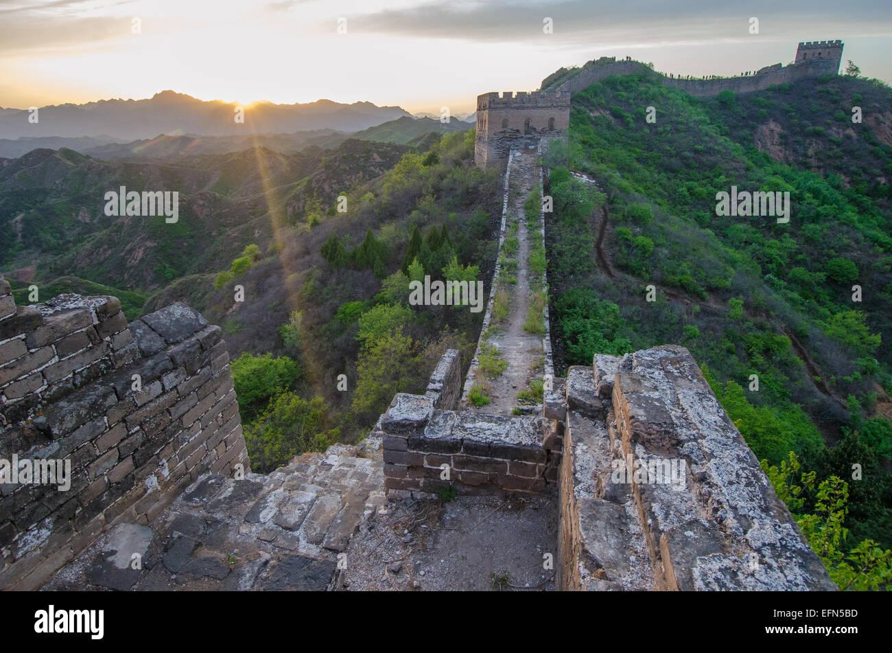 Die 2.300 Jahre alte chinesische Mauer wird von der untergehenden Sonne beleuchtet. Stockbild