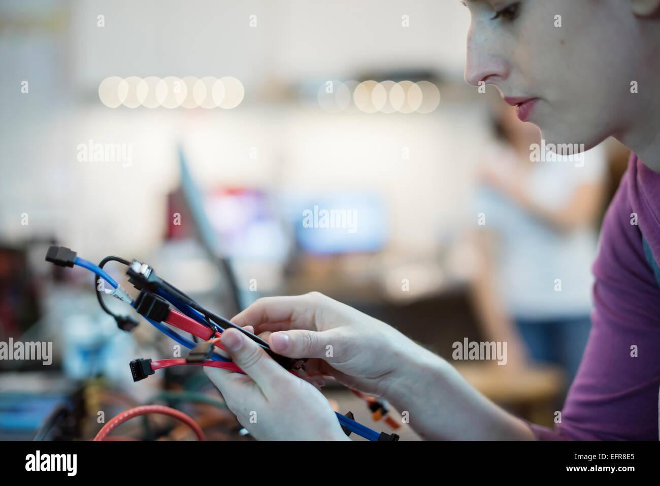 Eine junge Frau mit verbindenden Kabel und USB-führt in ein Computer-Werkstatt. Stockbild