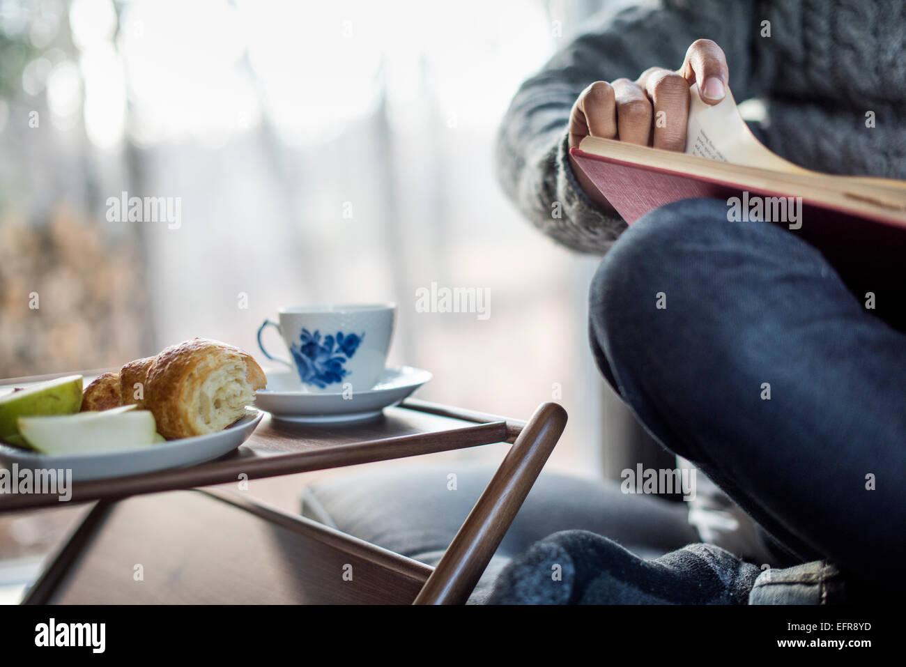 Mann ein Buch über seine Knie-Tasse und Untertasse und eine Platte Apple und Croissant neben ihm Ausgleich. Stockbild