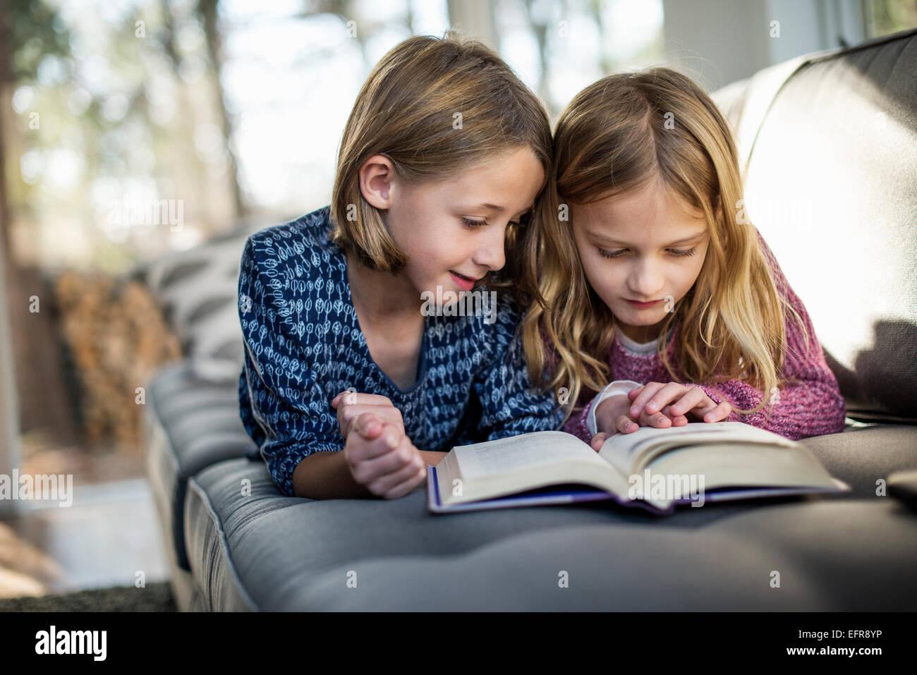 Zwei blonde Mädchen auf einem Sofa liegend ein Buch betrachten. Stockbild