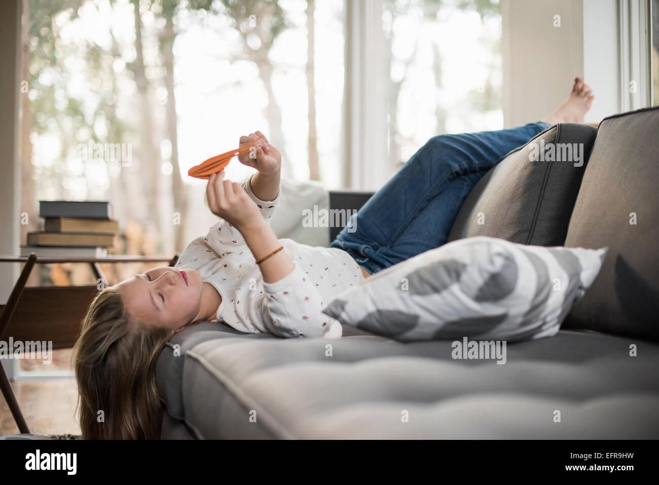 Mädchen auf einem Sofa auf dem Rücken liegend einen Papier Vogel hält. Stockbild