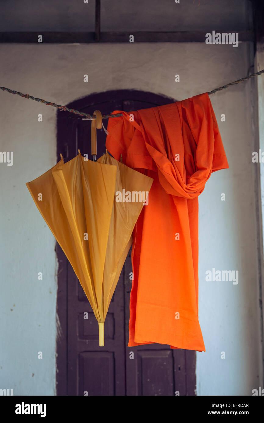 Orangefarbene Robe und Regenschirm hängend, Luang Prabang, Laos. Stockbild