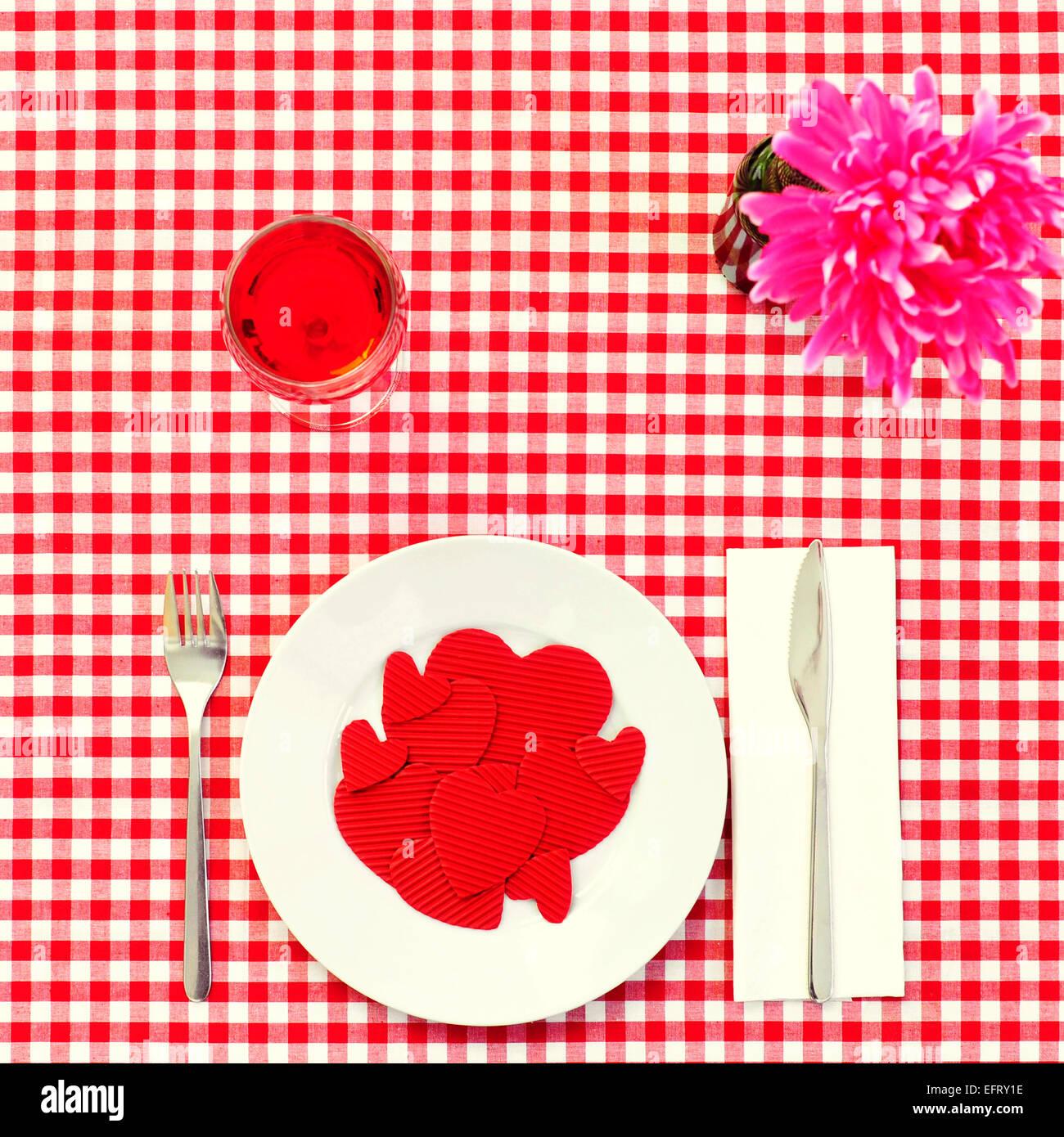 High-Angle Shot von einem Teller voller roten Herzen mit unterschiedlicher Größe auf einem gedeckten Tisch Stockbild