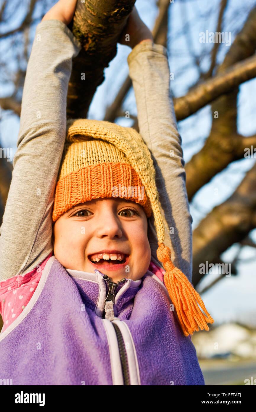 Junges Mädchen schwingen auf einem Ast im Herbst tragen gestrickte Zipfelmütze. Stockfoto