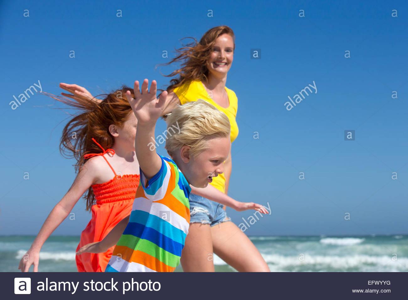 Mutter, Tochter und Sohn, ausgestreckten, läuft am Sonnenstrand Stockbild
