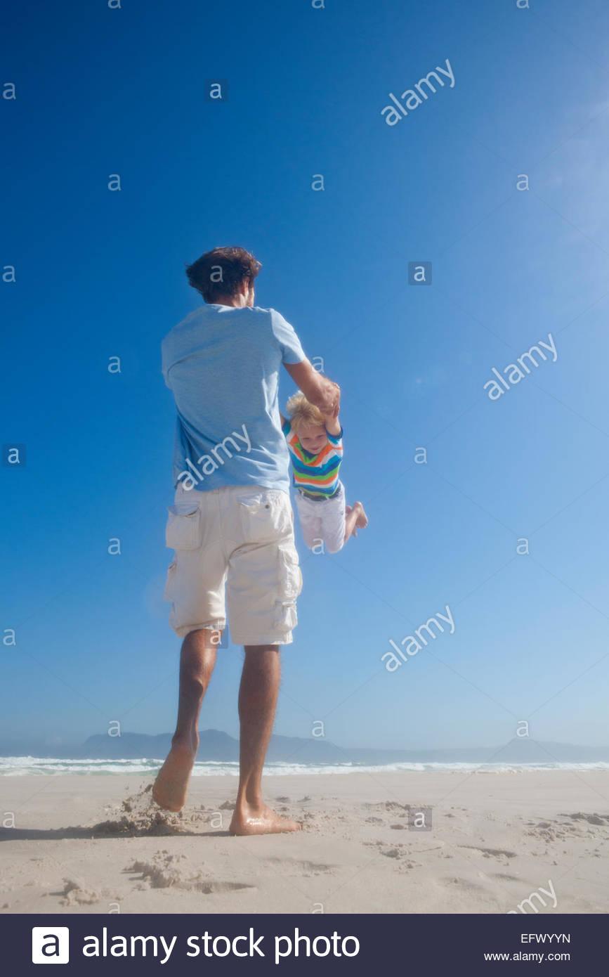 Vater schwingenden Sohn in der Luft spielerisch am Sonnenstrand Stockbild