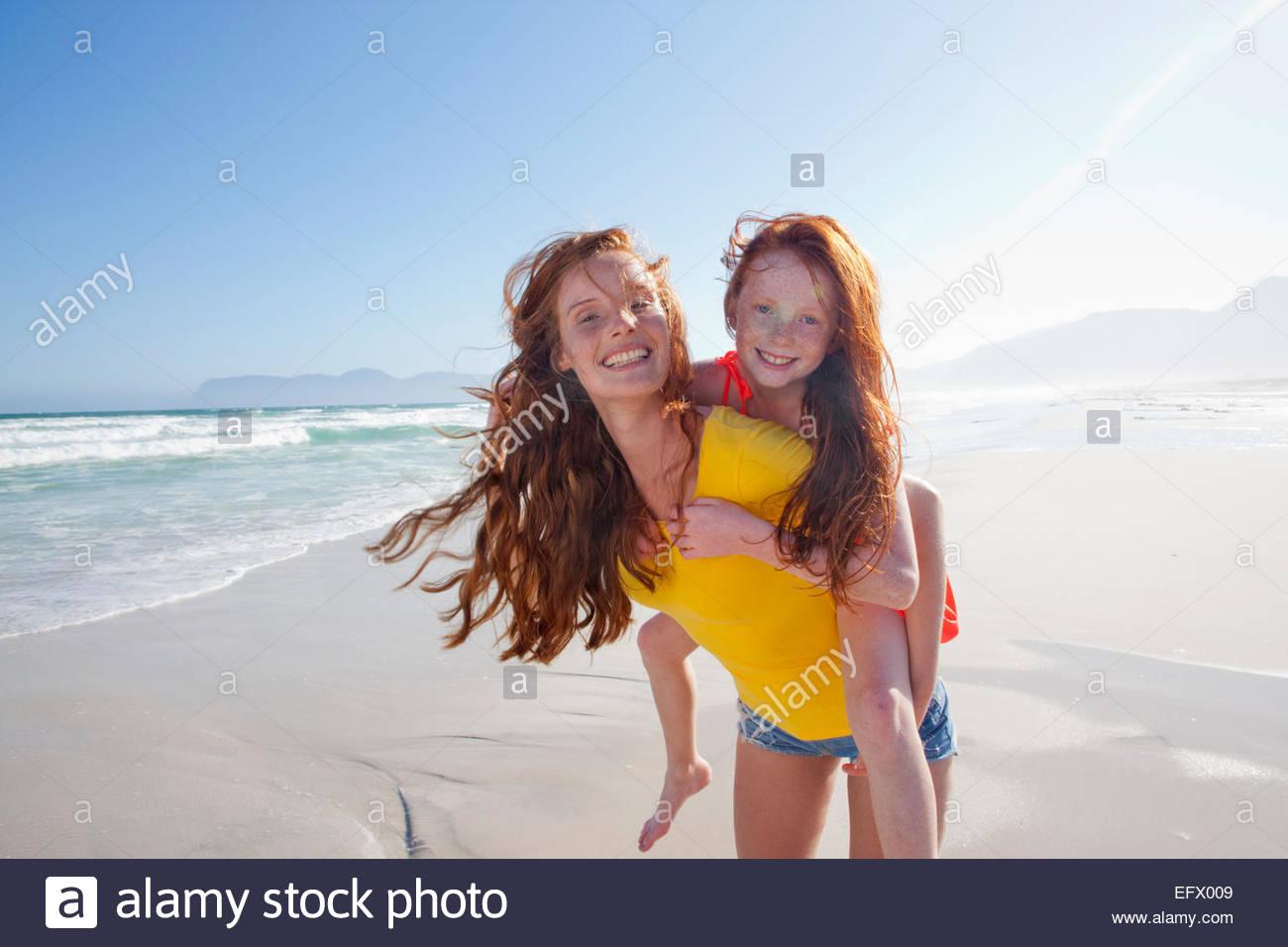 Lächelnde Mutter gibt Tochter Huckepack am Sonnenstrand Stockbild