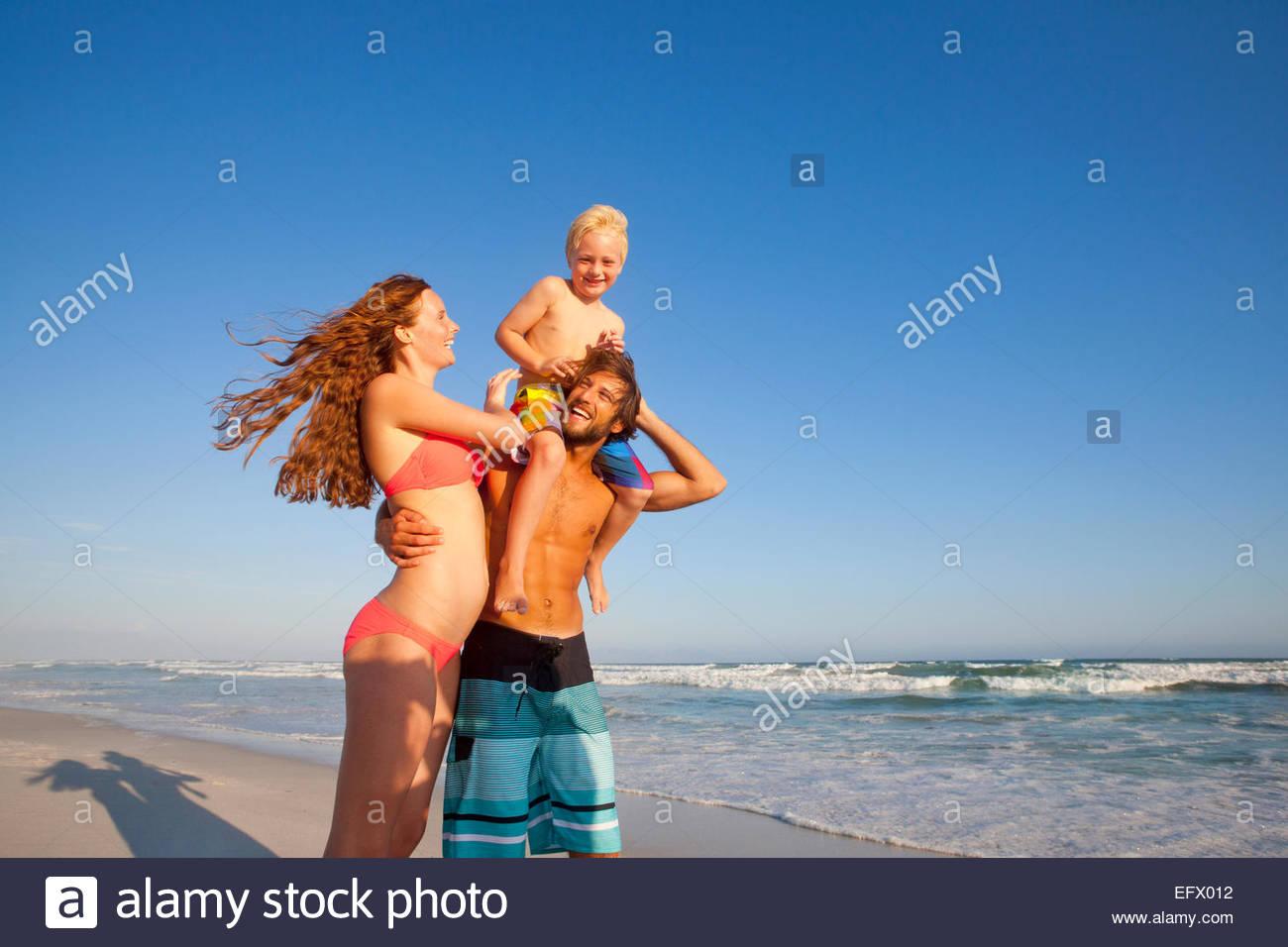 Glückliches Paar mit Sohn auf Vaters Schultern, am sonnigen Strand Stockbild