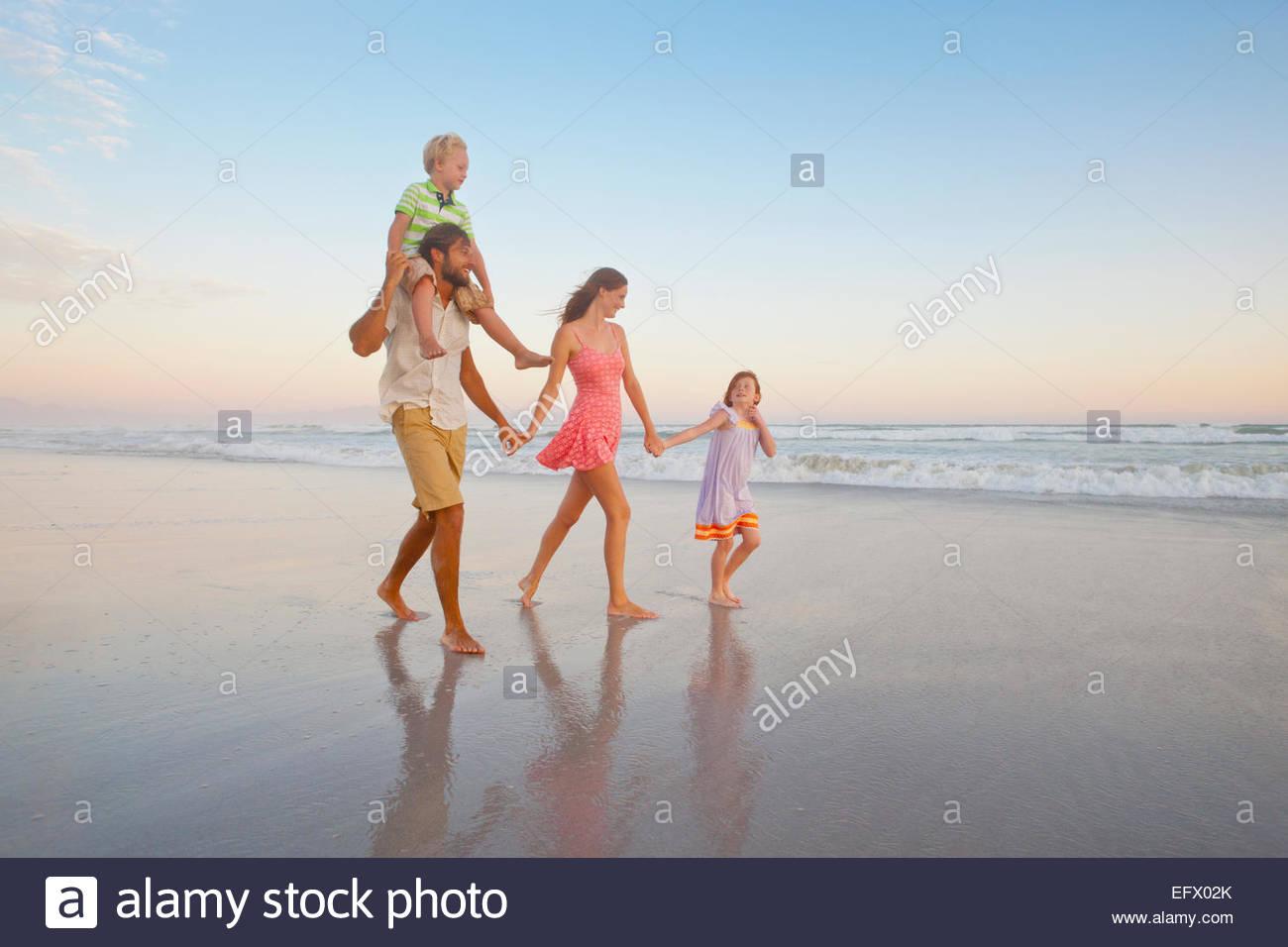 Glückliche Familie Wandern, halten Hände und Sohn mit Piggy-Backs, am sonnigen Strand Stockbild