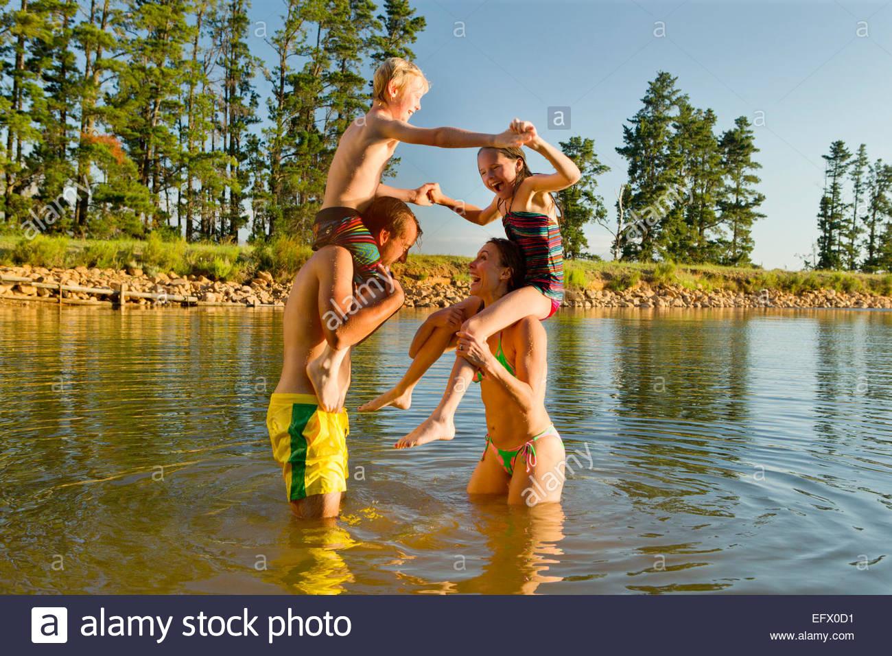 Glückliches Paar mit Kindern auf Schultern, mit Wasser zu kämpfen, im See Stockbild
