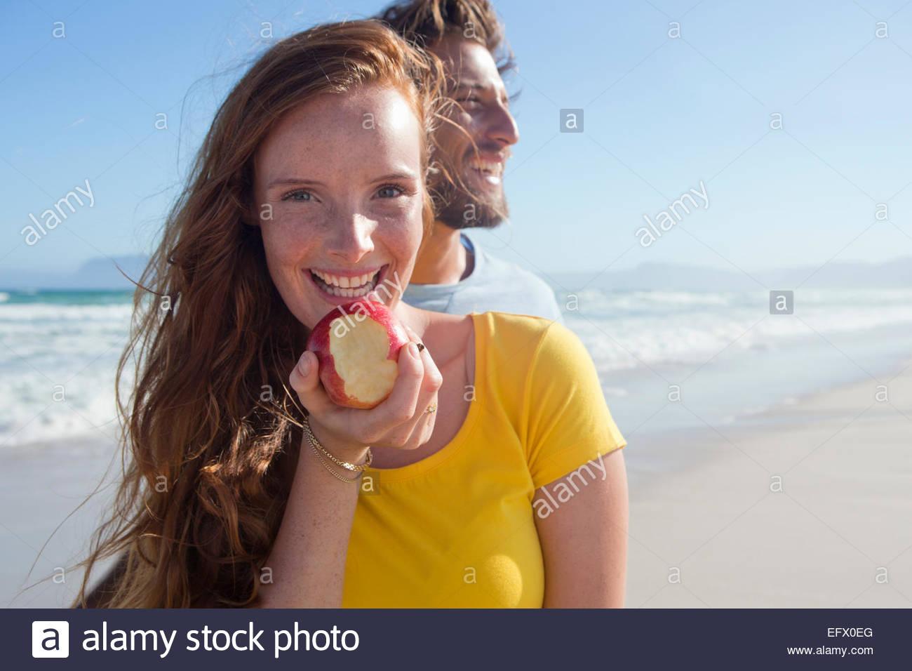 Lächelnde paar am Sonnenstrand, mit Frau hält einen Apfel mit einem Bissen aus ihm heraus Stockbild