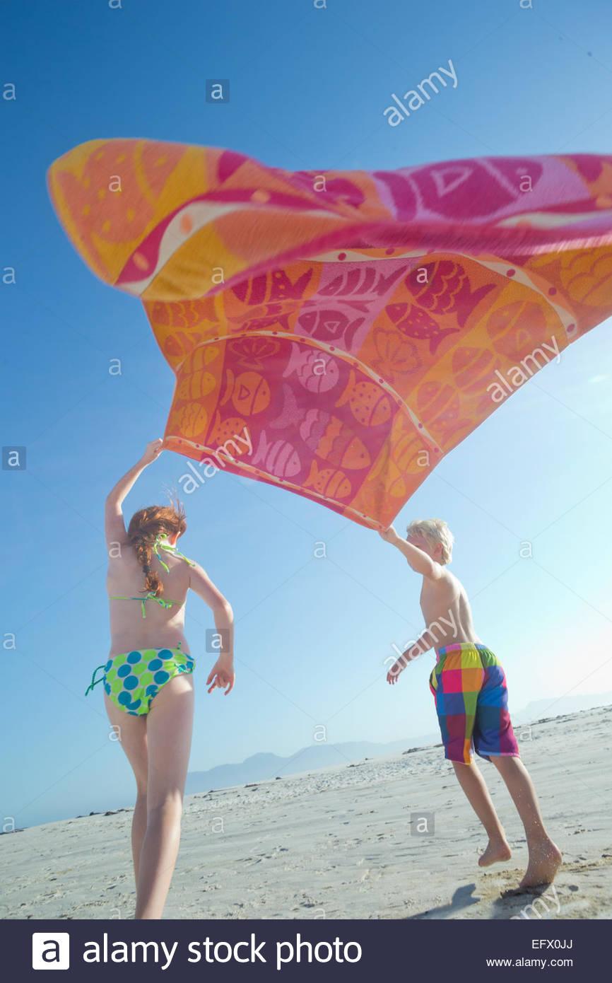 Jungen und Mädchen mit Handtuch über dem Kopf im Wind am Sonnenstrand Stockbild