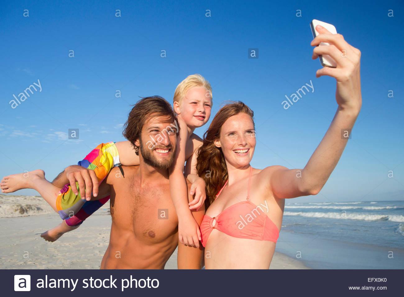 Porträt des glücklichen Paares mit Sohn auf Schulter, wobei Selfie am Sonnenstrand Stockbild