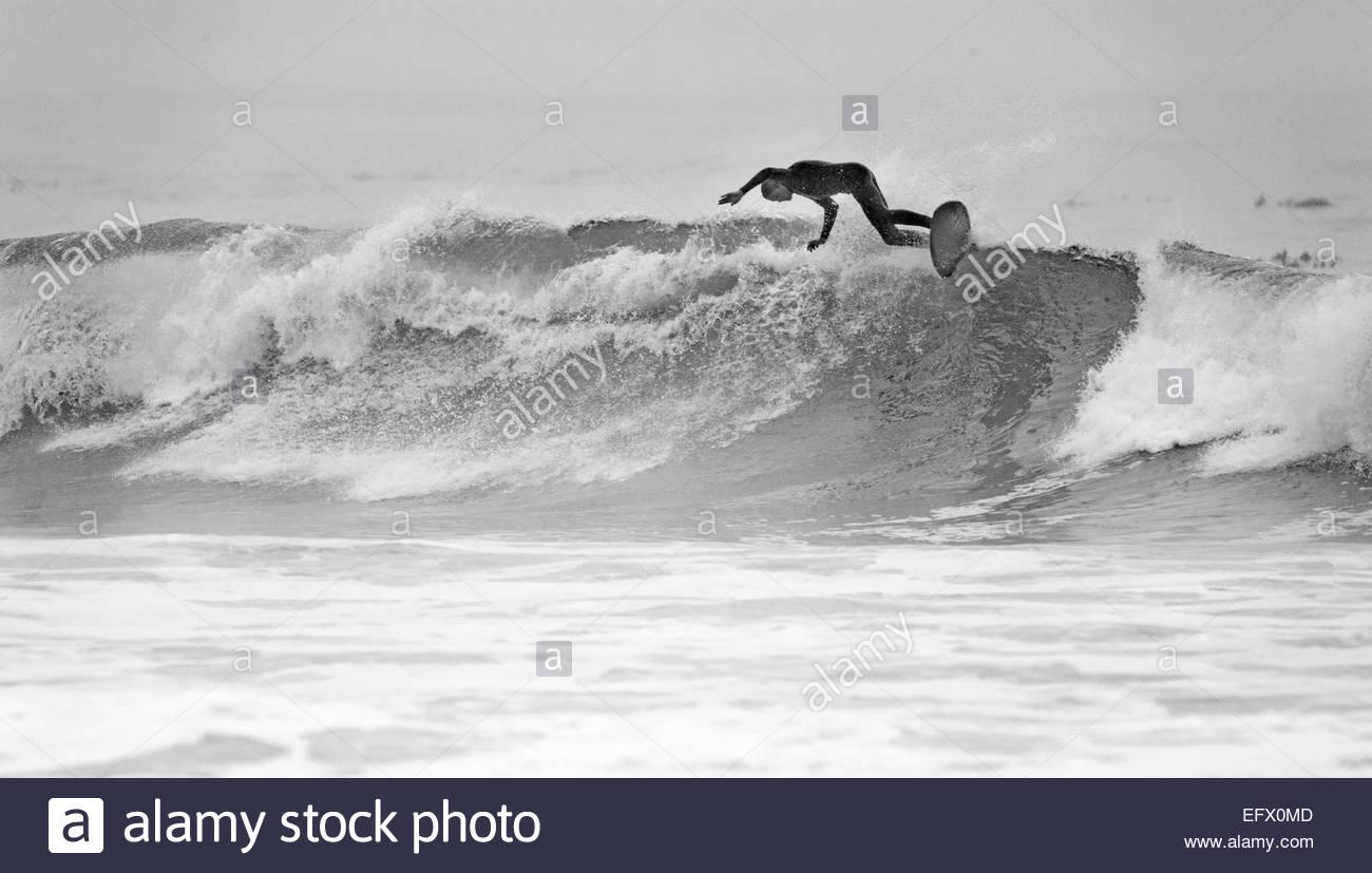 Surfer am Surfbrett auf Welle Stockbild