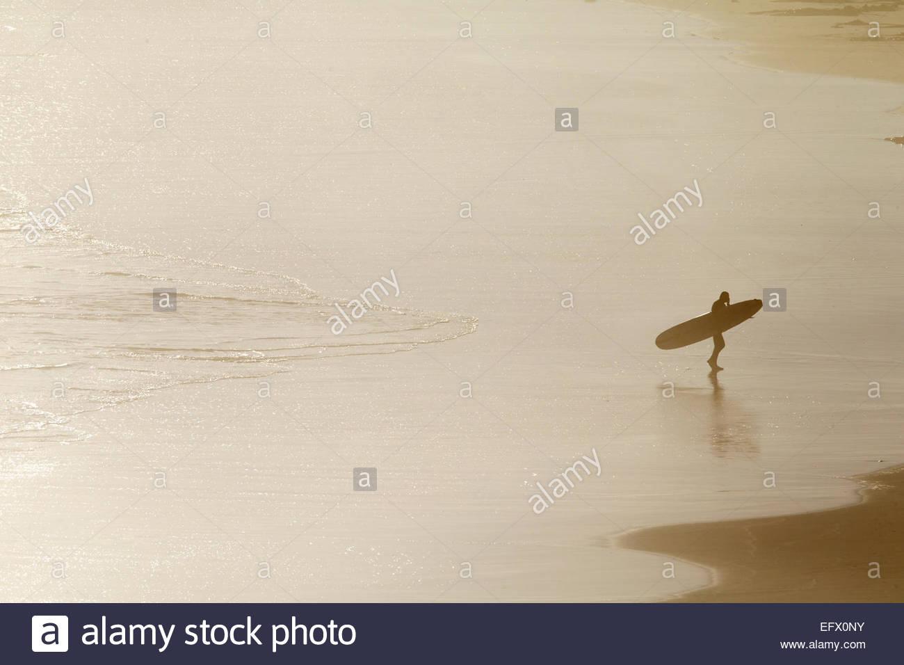 Surfer mit Surfbrett, vom Meer Strand entlang spazieren Stockbild