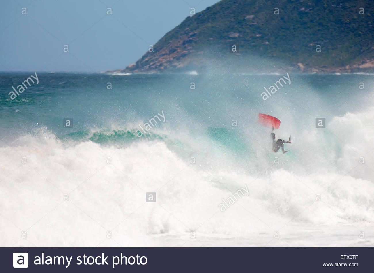 Surfer, die herunterfallen Bodyboard auf Welle Stockbild