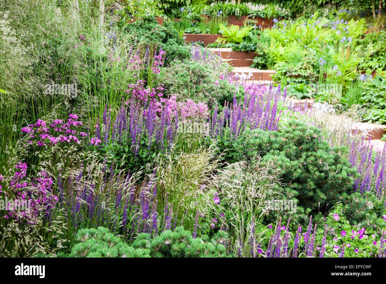 Kies mit Corten-Stahl durch abfallenden Garten mit Gräsern, kleine ...
