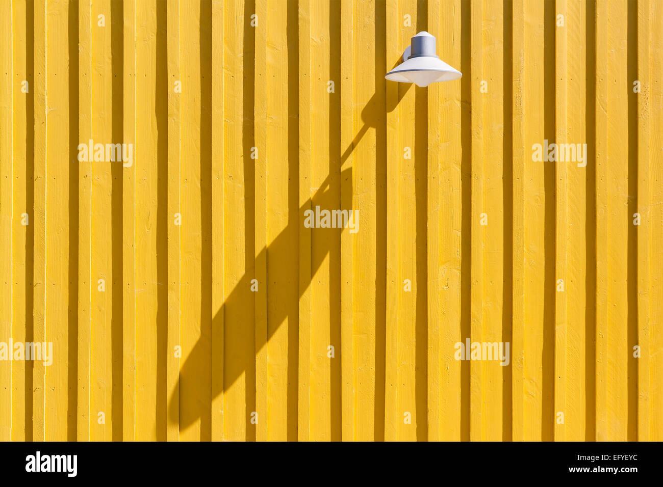 Lampe auf eine gelbe Strandhütte wirft einen langen Schatten, Île d'Oléron, Charente Maritime, Stockbild