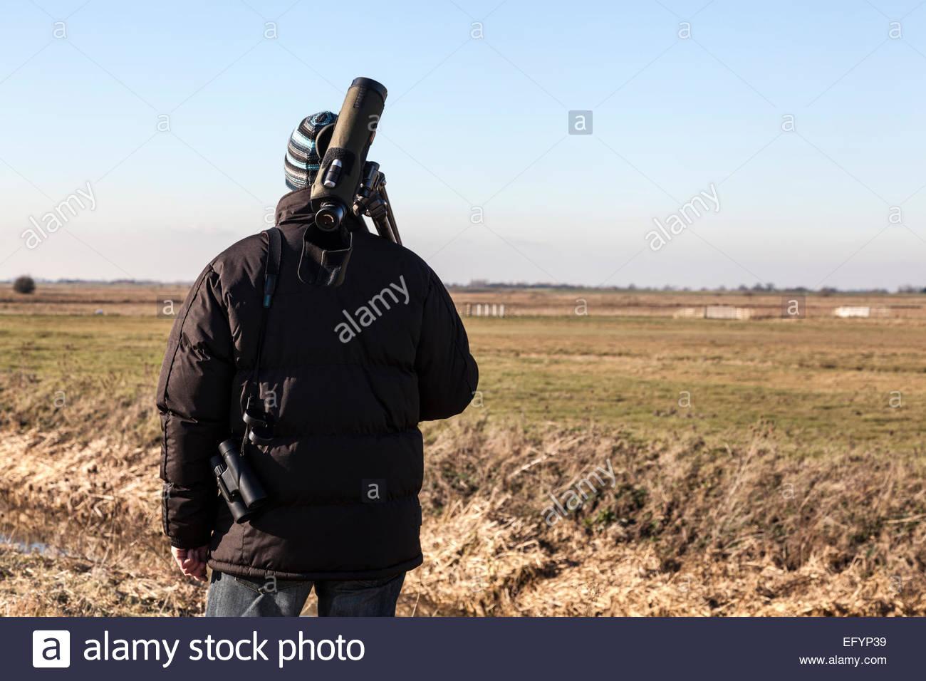 Mann mit fernrohr und fernglas für die vogelbeobachtung bei