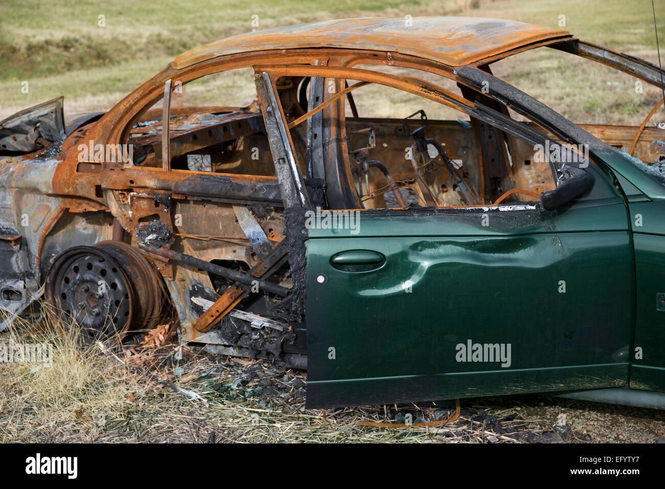 Grünes Auto durch einen Brand zerstört Stockbild