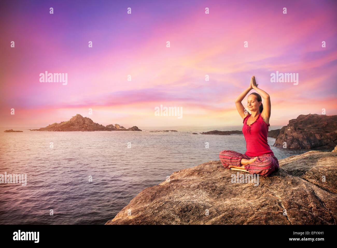 Frau tun Meditation im roten Kostüm auf dem Stein in der Nähe des Ozeans in Gokarna, Karnataka, Indien Stockfoto