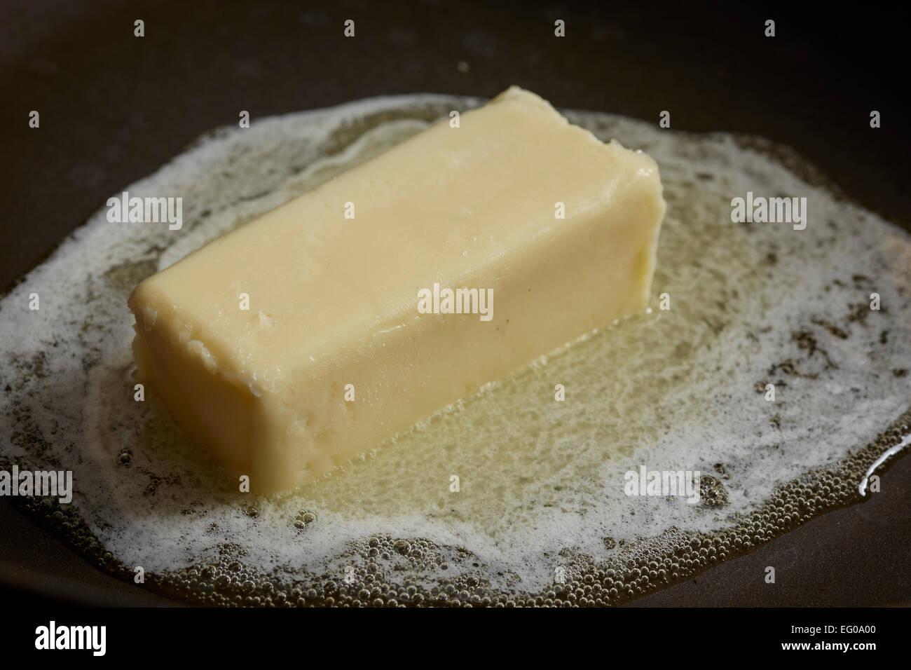 Butter in einer Pfanne schmelzen Stockbild