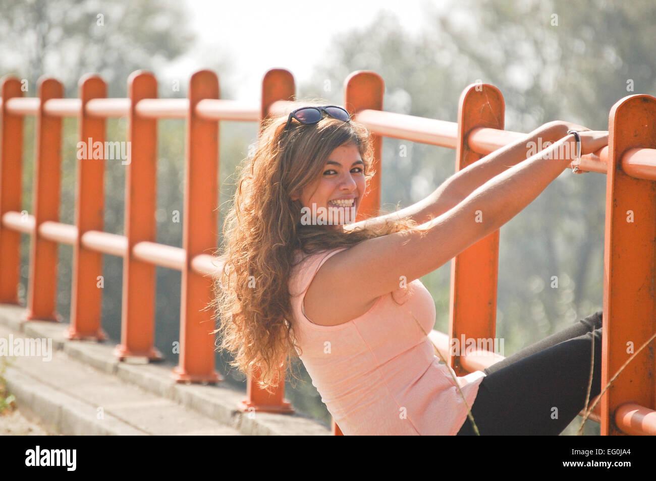 Langhaarige Frau stützte sich auf orange Barriere und lächelnd zu Kamera Stockbild