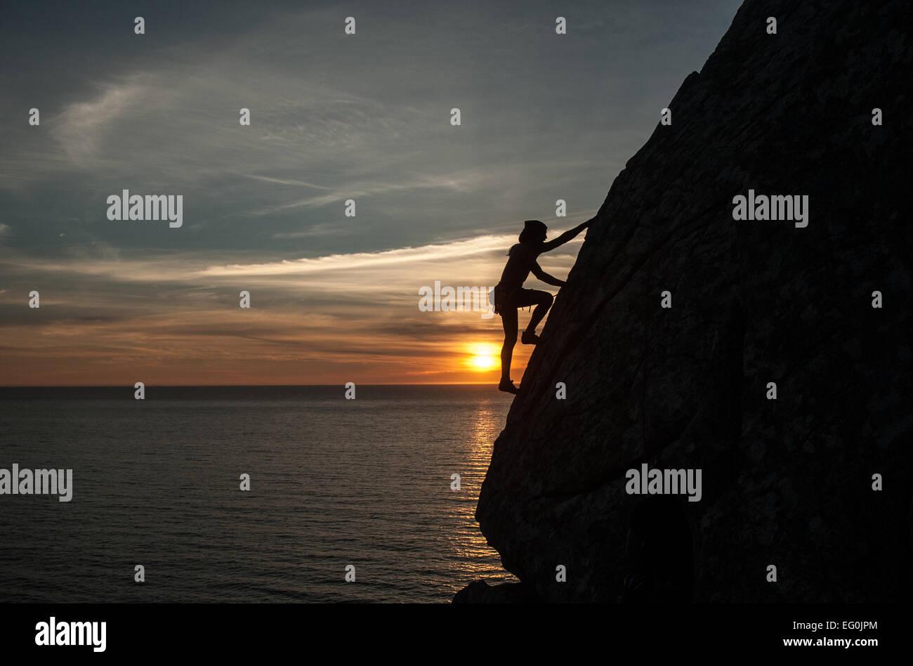 Silhouette der Frau Klettern Klippe bei Sonnenuntergang, Galicien, Spanien Stockbild