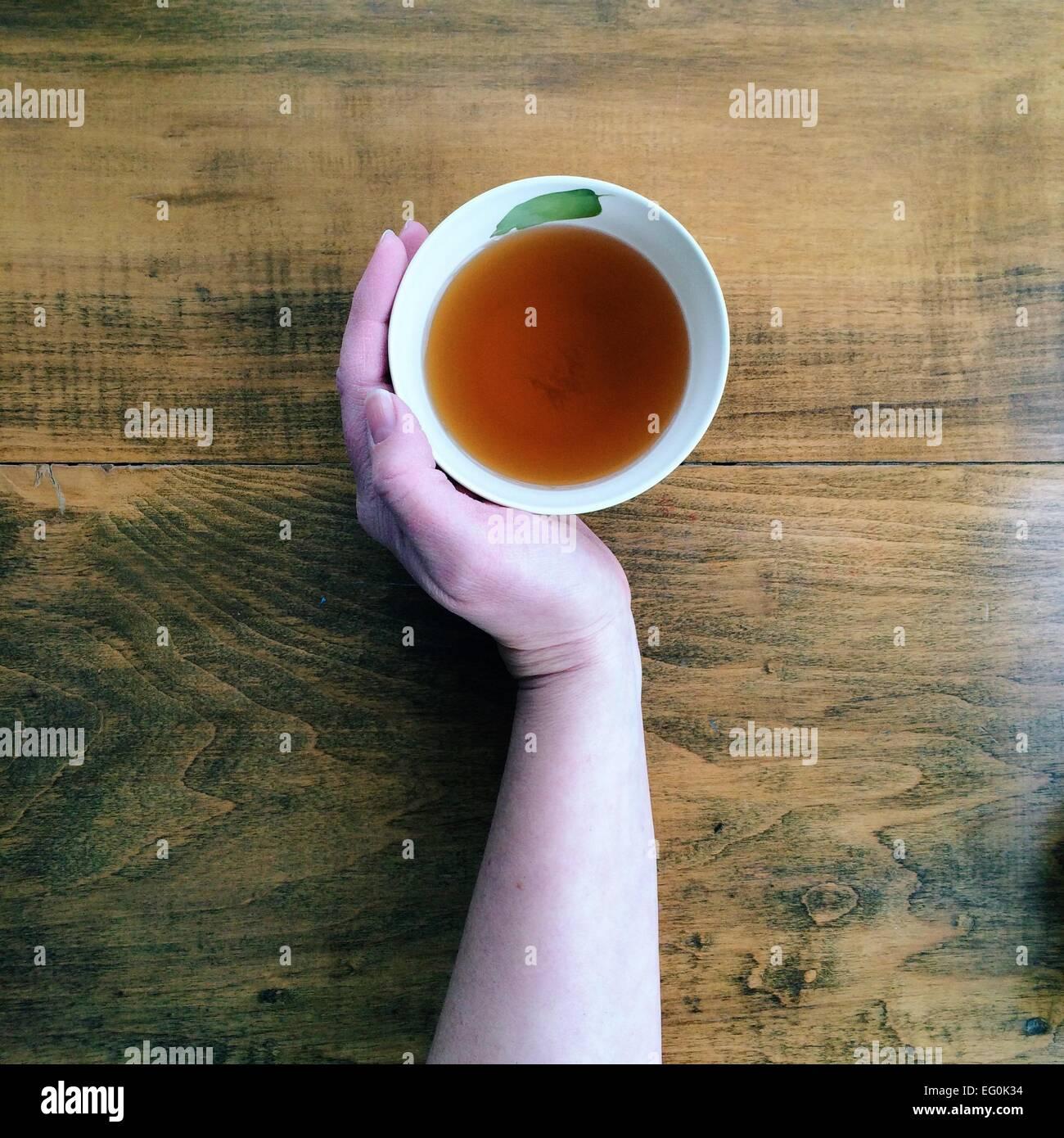 Hand mit Tasse Tee Stockbild