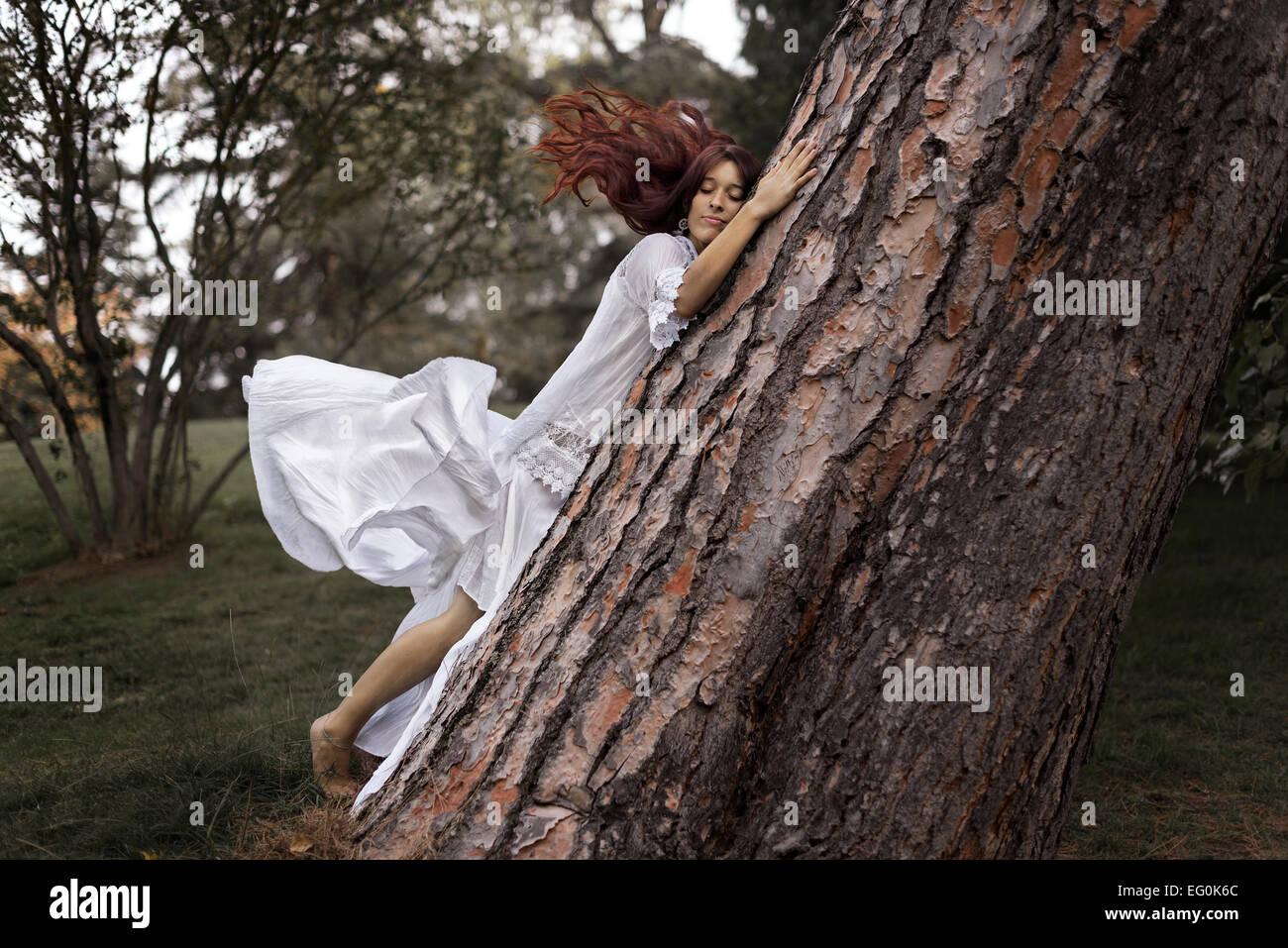 Schöne Frau umarmt einen Baum Stockfoto