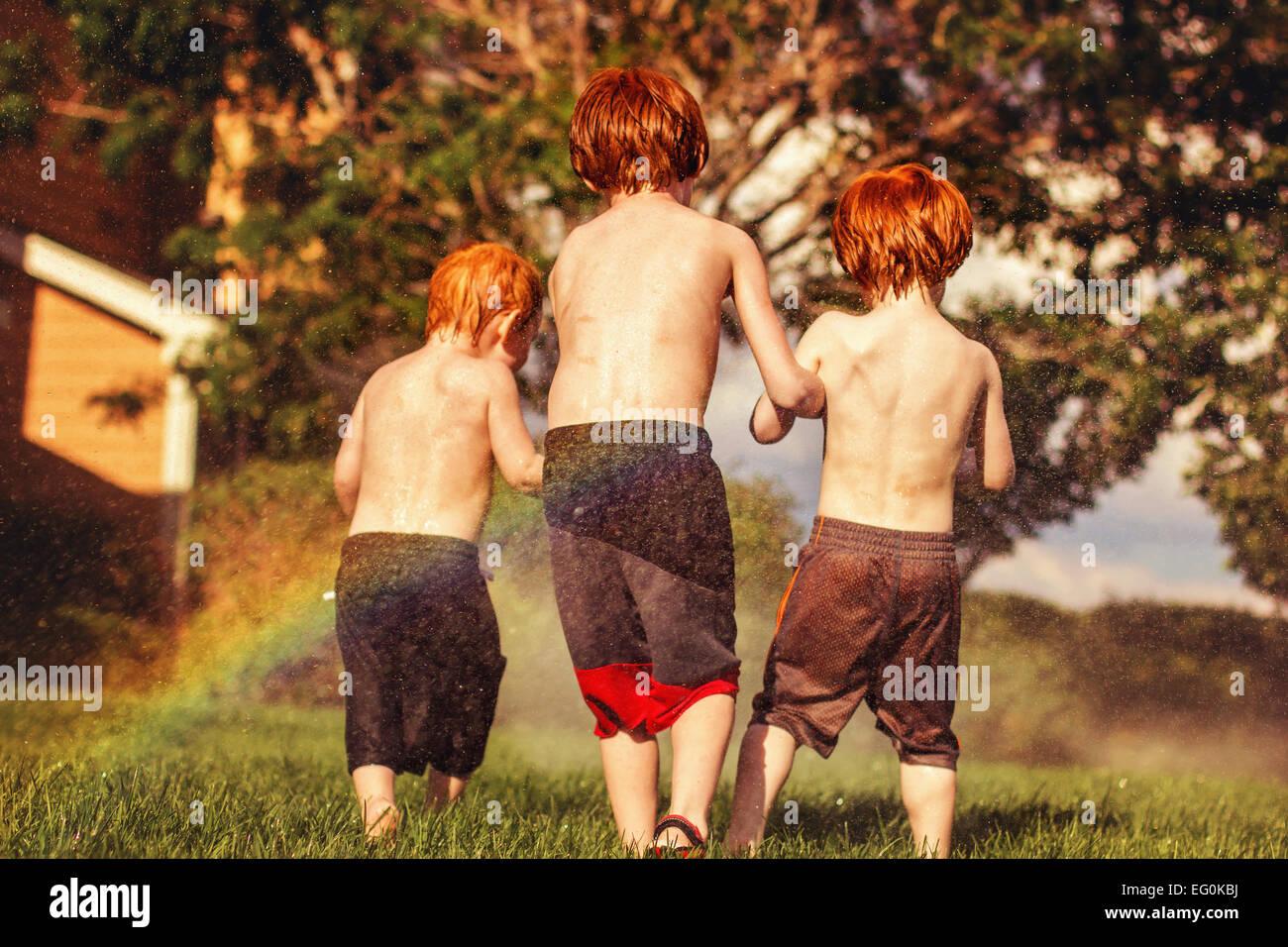 Drei junge Brüder spielen im Wasser Sprinkler Stockfoto