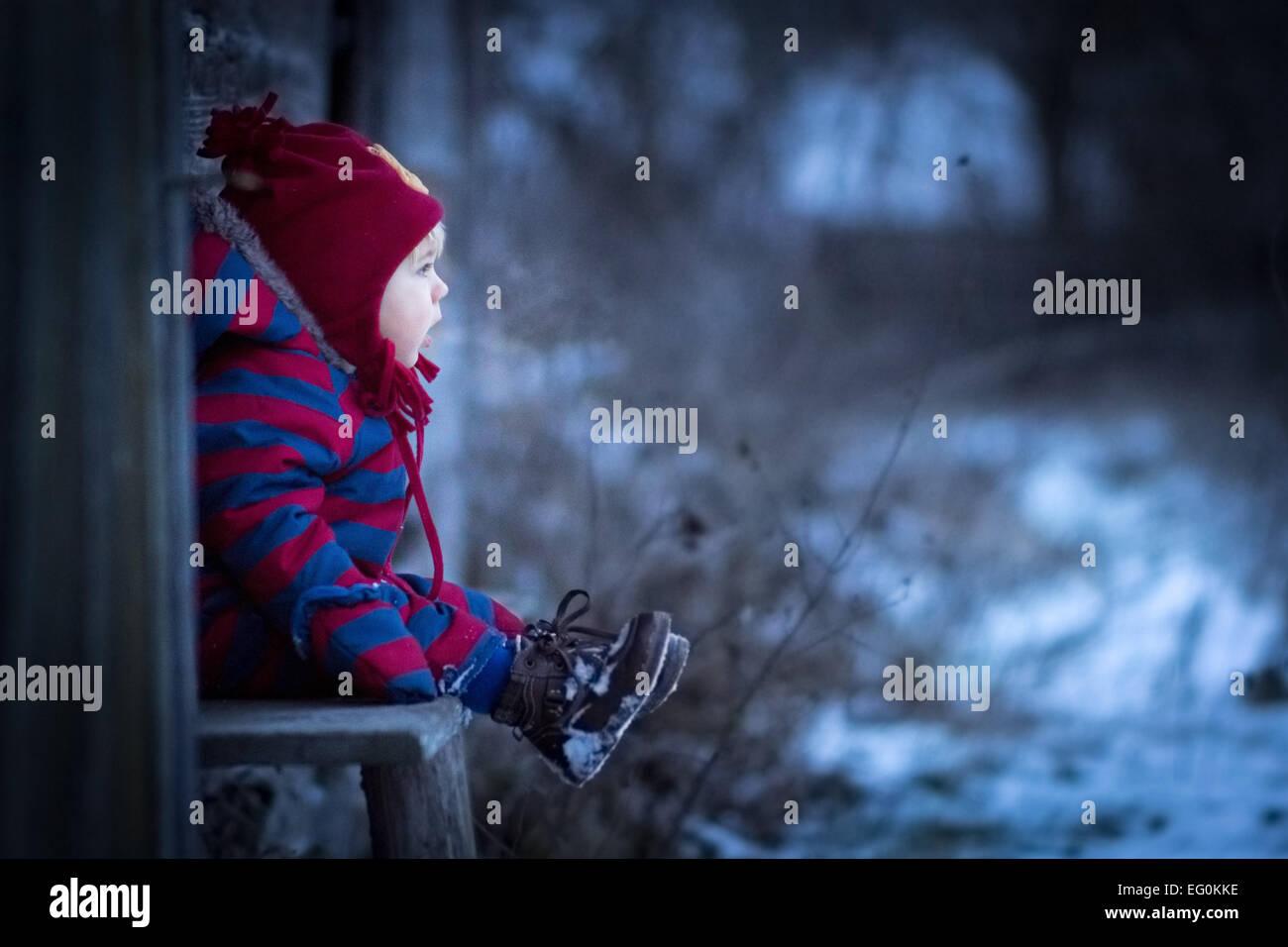 Kleiner Junge sitzt auf der Bank außerhalb Stockfoto
