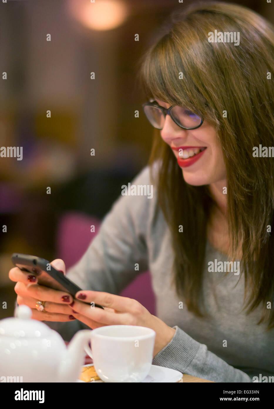 Schöne junge Frau, die Überprüfung ihres Mobiltelefons während ein heißes Getränk Stockbild