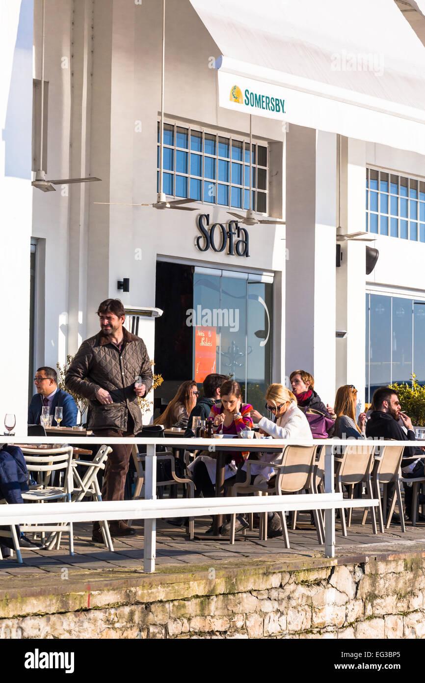 Personen im Gespräch an einem Tisch vor einem Restaurantbar, während ein Mann vorbei, im trendigen Viertel Stockbild