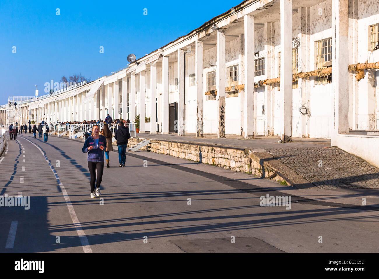 Eine junge Frau sieht man läuft vor einer stillgelegten Lagerhalle in der Waterfront sind von Savamala, Beton Stockbild