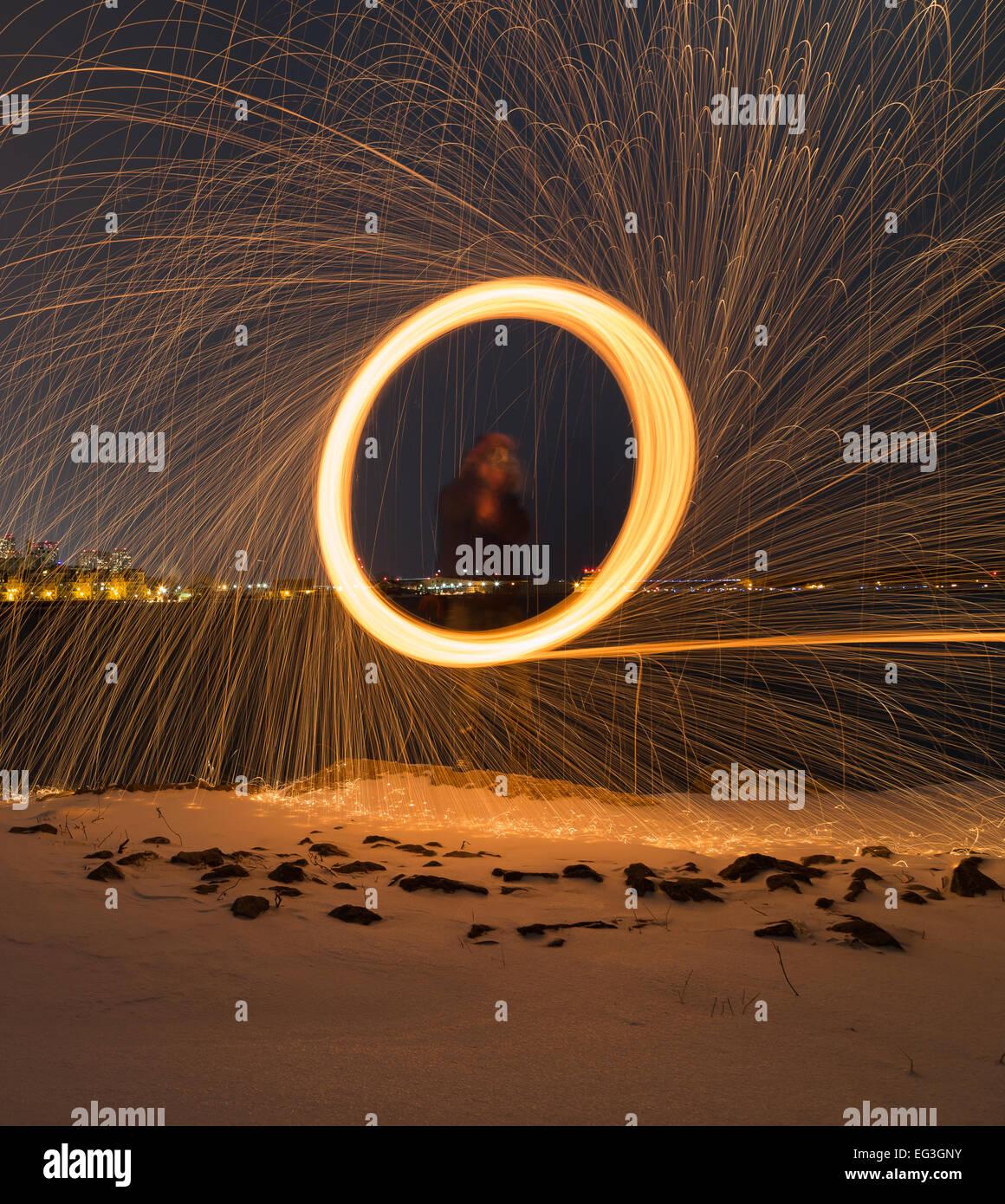 Ein Mann Spinnen Wolle draußen in der Nacht mit Exemplar am unteren Stockfoto