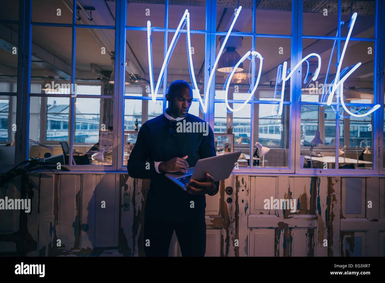Afrikanischen jungen Mann im Büro mit Laptop-Computer. Führungskraft im Büro mit großen Neonlicht Stockbild