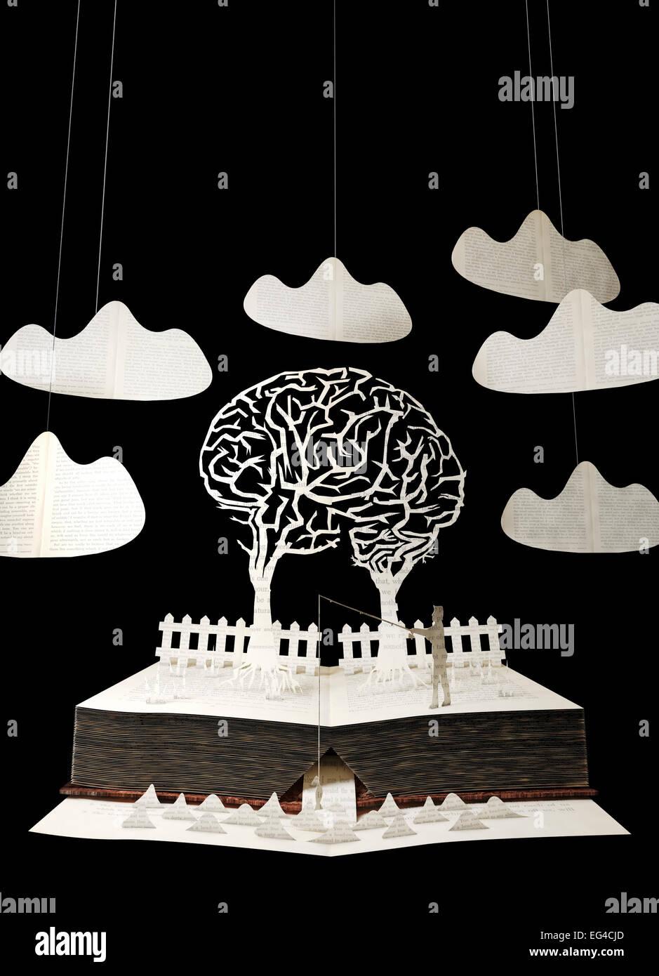 Landschaft aus Buch zu schneiden. Zwei Bäume Efeuranken machen Gehirn. Mann Angeln im Vordergrund. Zaun im Stockbild