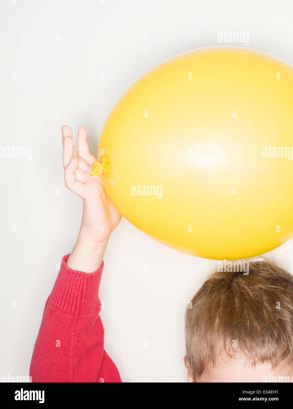 Kind mit gelben Ballon über Haare. Lustige Kindheit Wissenschaft experimentieren mit Strom. Stockbild