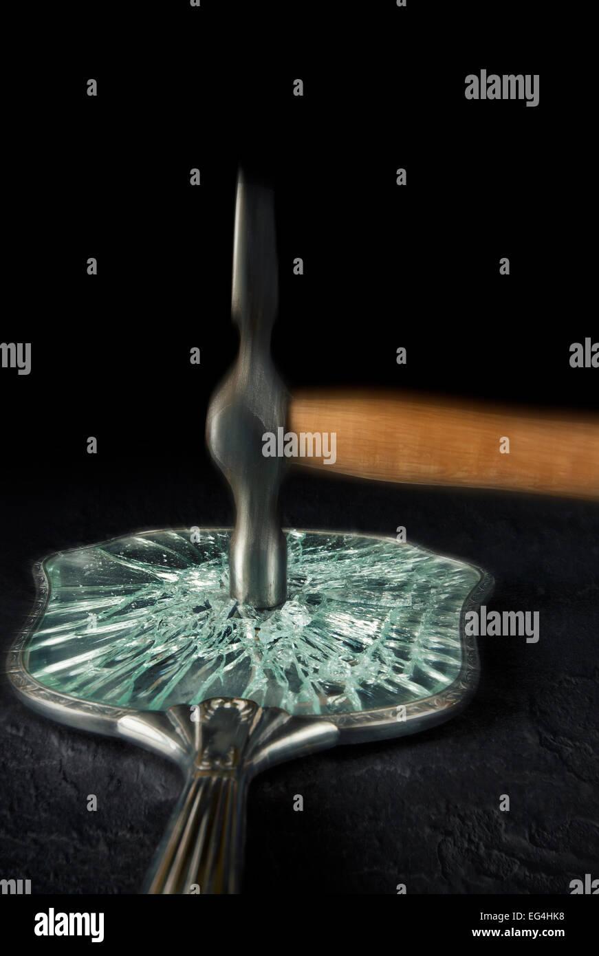 Hammer zertrümmern einen Kosmetikspiegel. Stockbild