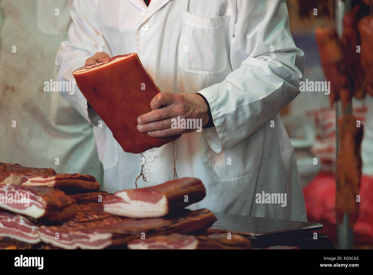 Metzger auf Schwein Fleisch Fair mit Stapeln von geräuchertem Speck und andere geheilt Schweinefleisch. Stockbild