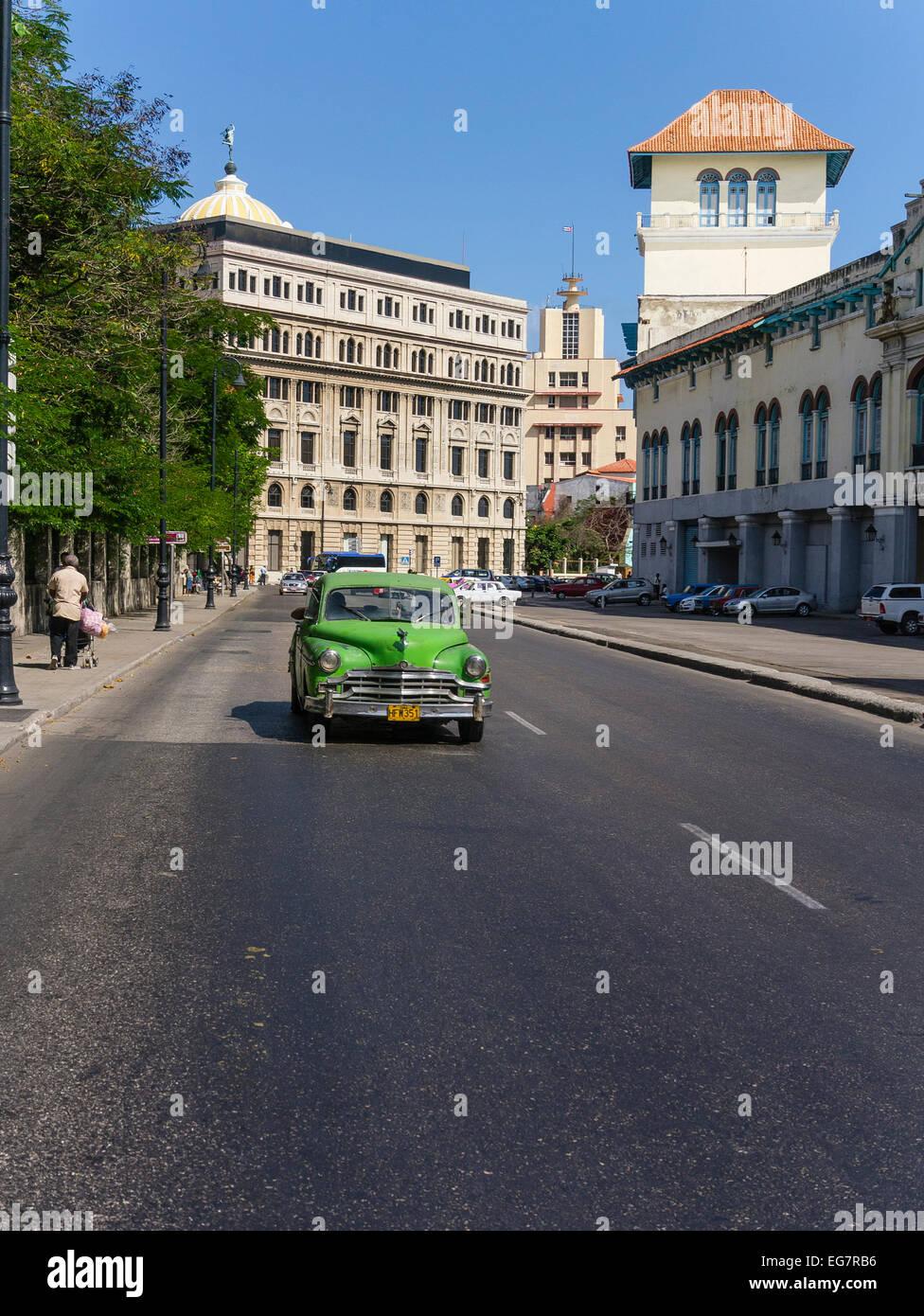 Altes grünes Auto mit orange Nummernschild fahren auf Straße in Havanna, Kuba. Stockbild
